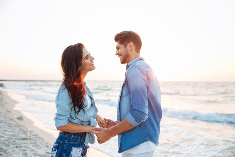 Happy young couple holding hands and laughing on the beach