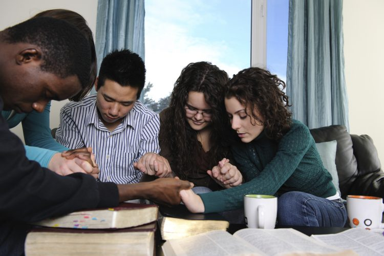 College students praying together while holding hands.